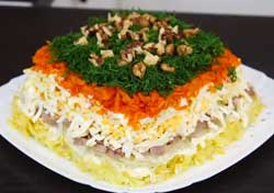 Украшаем салат из консервированной печени укропом и орехами.